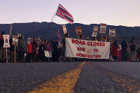 Demonstrators are gather to block a road at the base of Hawaii's tallest mountain, on July 15, 2019, in Mauna Kea, Hawaii, to protest the construction of a giant telescope on land that some Native Hawaiians consider sacred. (AP Photo/Caleb Jones)