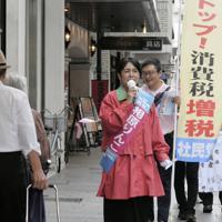 「ストップ消費税増税」と書かれたのぼりとともに、暮らしを守る政策を訴える相原氏=横浜市中区で