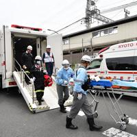 「京都アニメーション」の火災で救護所が設けられ、負傷者をストレッチャーに乗せて運ぶ救急隊員ら=京都市伏見区で2019年7月18日午後0時46分、川平愛撮影