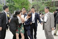 A woman, third from left, is restrained by plainclothes police officers after shouting,