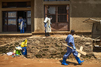 In this photograph taken on July 14, 2019, a morgue employee walks with a cross past others disinfecting the entrance to the morgue in Beni, Congo DRC. (AP Photo/Jerome Delay)