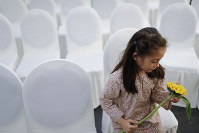 A girl holds a flower as friends and family of victims from Malaysia Airlines Flight MH17 plane crash attend a ceremony marking the fifth anniversary of the tragedy in Kuala Lumpur, Malaysia, on July 17, 2019. (AP Photo/Vincent Thian)
