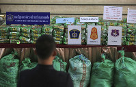 In this July 15, 2019 photo, reporters view packages of seized 459 kilograms of crystal methamphetamine on a table during a press conference at Narcotics Suppression Bureau in Bangkok, Thailand. (AP Photo)