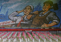 In this July 16, 2019, photo, North Koreans hold cards to make an image depicting a worker and a farmer during a mass game performance of
