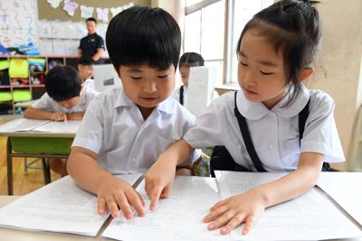 初めて受け取った通知表を見せ合う1年生の児童ら=東京都台東区の金竜小学校で2019年7月19日午前9時17分、北山夏帆撮影