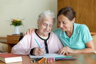 作業療法に取り組む高齢の女性(左)