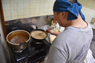 支援施設「金沢みんなのいえ」でトンカツを揚げる男性=金沢市諸江町で、日向梓撮影