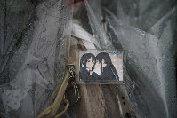 A keychain with a cartoon image is placed on top of flowers Friday, July 19, 2019, near the Kyoto Animation Studio building destroyed in an attack the previous day, in Kyoto, Japan. (AP Photo/Jae C. Hong)