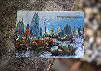 Kim Draper received a postcard, which depicts a scene of fishing boats in Hong Kong, at her home in Springfield on July 8, 2019 that was postmarked and sent from Hong Kong exactly 26 years ago on July 8, 1993 to a previous family that lived at her address. (Justin L. Fowler/The State Journal-Register via AP)