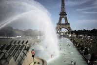 People cool off in the fountains of the Trocadero gardens, in front of the Eiffel Tower, in Paris, on June 28, 2019. (AP Photo/Lewis Joly)