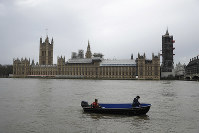 In this Jan. 31, 2018 file photo, people aboard a boat make way past the Houses of Parliament with Big Ben's clock tower, the Elizabeth Tower covered in scaffolding for repairs in London. (AP Photo/Matt Dunham)