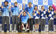 Uniforms for Tokyo Olympics and Paralympics volunteers are unveiled on July 19, 2019, in Tokyo's Chuo Ward. Former SMAP member Shingo Katori, center, a uniform selection committee member, is seen smiling. The uniforms seen on the left will be worn by volunteers at the tournament, and the uniforms on the right will be worn by volunteers in the city. (Mainichi/Junichi Sasaki)