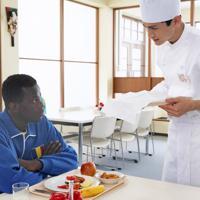 選手村の食堂でチャドから来た選手に話しかける三郎(高良健吾=右)