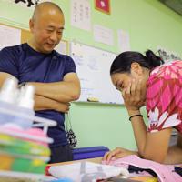 卓球部女子監督の松井伸英さん(左)と練習の相談をするサリーさん。松井さんは「私のこと、おじいちゃんて呼ぶんですよ」と笑った=長崎県諫早市で2019年6月16日、宮武祐希撮影
