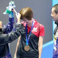 混合デュエット・フリールーティン決勝で3位となりメダルを花牟礼雅美コーチ(中央)にかける足立夢実(左)。右は安部篤史=韓国・光州で2019年7月20日、宮武祐希撮影