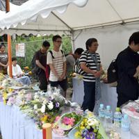 放火事件の現場近くに新たに設置された献花台に多くの人たちが訪れ、手を合わせた=京都市伏見区で2019年7月20日午後2時26分、平川義之撮影