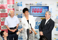 This file photo taken on Aug. 18, 2018, shows Kankeiren Chairman Masayoshi Matsumoto, right, Hyogo Gov. Toshizo Ido, left, and TV star So Takei, center, appearing in front of a display for the 2021 World Masters Games in Kansai set up at a lobby at Kansai International Airport in commemoration of the 1,000-day countdown to the start of the competition. (Mainichi/Kentaro Ikushima)