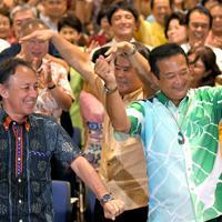 当選が確実になりカチャーシーを踊る高良鉄美氏(右)。左は沖縄県の玉城デニー知事=那覇市で2019年7月21日午後8時2分、津村豊和撮影