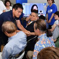 厳しい表情で支持者と握手する辰巳孝太郎氏(左)=大阪市中央区で2019年7月21日午後8時40分、木葉健二撮影
