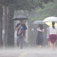 激しく地面を叩く雨で足下が白くかすむ中を歩く人たち=福岡市中央区で2019年7月21日午前11時58分、須賀川理撮影