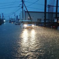冠水した道路を通行する車両=福岡県久留米市梅満町で2019年7月21日午前5時半ごろ、安部志帆子撮影
