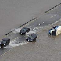 道路脇で横倒しになった車の横を水しぶきを上げて進む車両=福岡県大刀洗町で2019年7月21日午後3時50分、本社ヘリから須賀川理撮影