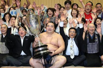 優勝し賜杯を手に笑顔を見せる鶴竜(中央)=ドルフィンズアリーナで2019年7月21日、兵藤公治撮影