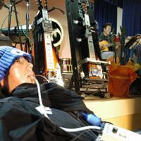 舩後靖彦さん(手前)は定期的に自らのバンドの演奏会も開いている。歯でかむセンサーから読み取られた情報をもとに、壇上に並ぶギターの弦が和音を奏でる=千葉県松戸市で2019年7月6日午後6時25分、山下貴史撮影