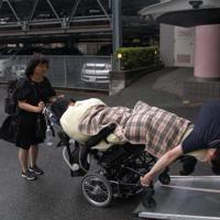 第一声の会場に向かうため、自宅マンションの駐車場から車に乗り込む舩後靖彦さん(中央)。体が冷えないよう布団でくるまれている=千葉県松戸市で2019年7月12日午後2時39分、山下貴史撮影