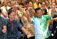 Tetsumi Takara, right, performs a traditional dance in Okinawa Prefecture, with Gov. Denny Tamaki, left, in Naha after he was heading for victory in the House of Councillors election on July 21, 2019. (Mainichi/Toyokazu Tsumura)