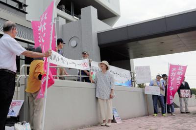 千葉県鴨川市役所前で、メガソーラーの建設反対を訴える「鴨川の山と川と海を守る会」の勝又国江代表(中央)ら