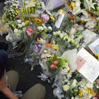 火災現場近くで献花し、手を合わせる人たち=京都市伏見区で2019年7月19日午後5時38分、平川義之撮影