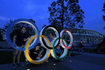 夕暮れの五輪モニュメントで、記念撮影する人たち。奥は建設が続く新国立競技場=東京都新宿区で2019年7月18日、手塚耕一郎撮影