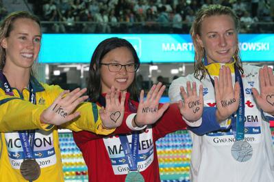 女子100メートルバタフライの表彰式で、池江璃花子へのメッセージを手に書いた(左から)エマ・マキオン、マクネル・マーガレット 、サラ・ショーストロム=韓国・光州で2019年7月22日、宮武祐希撮影
