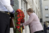 German Chancellor Angela Merkel adjusts a wreath during a memorial event at the Defence Ministry in Berlin, Germany, on July 20, 2019. (AP Photo/Michael Sohn)