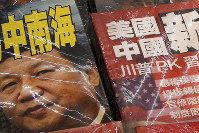 In this July 4, 2019, photo, magazines with front covers featuring Chinese President Xi Jinping with South China Sea and Xi against U.S. President Donald Trump are placed on sale at a roadside bookstand in Hong Kong. (AP Photo/Andy Wong)
