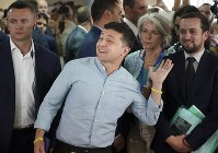 Ukrainian President Volodymyr Zelenskiy, center, gestures as he arrives at a polling station during a parliamentary election in Kiev, Ukraine, on July 21, 2019. (AP Photo/Evgeniy Maloletka)