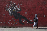 A woman walks past a mural on a sidewalk in Tehran, Iran, on July 21, 2019. (AP Photo/Vahid salemi)