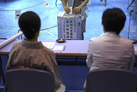 A voter casts a ballot in upper house elections as representatives of a local election administration commission observe at a polling station in Tokyo, on July 21, 2019. (AP Photo/Eugene Hoshiko)