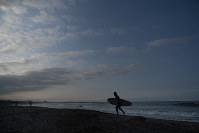 In this July 17, 2019, photo, a surfer walks out of the ocean at Taito Beach located next to Tsurigasaki, a venue for surfing at the Tokyo 2020 Olympics, in Isumi, Chiba prefecture, east of Tokyo. (AP Photo/Jae C. Hong)