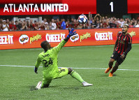 Atlanta United forward Josef Martinez scores a goal past D.C. United goalkeeper Bill Hamid for a 2-0 victory in a soccer match on July 21, 2019, in Atlanta. (Curtis Compton/Atlanta Journal-Constitution via AP)