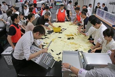 集まった投票箱から投票用紙を出し開票作業を行う千代田区の職員ら=東京都千代田区で2019年7月21日午後8時51分、山下浩一撮影
