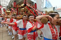 Young women carrying a portable shrine on their shoulders parade through the Tenjinbashisuji shopping arcade in Osaka's Kita Ward during the