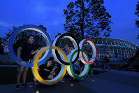 People are seen posing for photos among the Olympic rings set up outside the New National Stadium in Shinjuku Ward, Tokyo, on July 18, 2019. (Mainichi/Koichiro Tezuka)