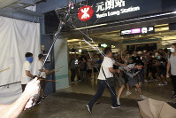 In this July 21, 2019 photo, thugs in white shirts armed with metal rods and wooden poles attack commuters at a subway station in New Territory in Hong Kong. (Apple Daily via AP)