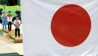 In this Aug. 10, 2016 file photo, a Japanese national flag hangs as gold medallist Kohei Uchimura, second from left, sings his national anthem during the artistic gymnastics men's individual all-around final at the 2016 Summer Olympics in Rio de Janeiro, Brazil. AP Photo/Dmitri Lovetsky)
