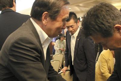 落選が確実となり、陣営関係者に謝罪する平野達男氏(左)=盛岡市のアートホテル盛岡で