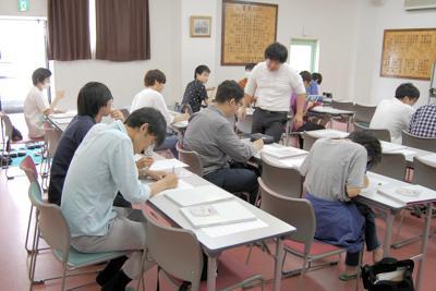 アンケートに回答する卒業生ら=埼玉県春日部市中央1の松実高等学園ホールで