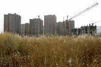 This July 6, 2019 photo shows residential towers in District 22, that consists of apartment high-rises and shopping malls arranged around an artificial lake called Chitgar, under construction on the northwestern edge of Tehran, Iran. (AP Photo/Ebrahim Noroozi)