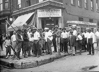 In this 1919 photo provided by Chicago History Museum, a crowd of men and armed National Guard stand in front of the Ogden Cafe during race riots in Chicago. (Chicago History Museum/The Jun Fujita negatives collection via AP)